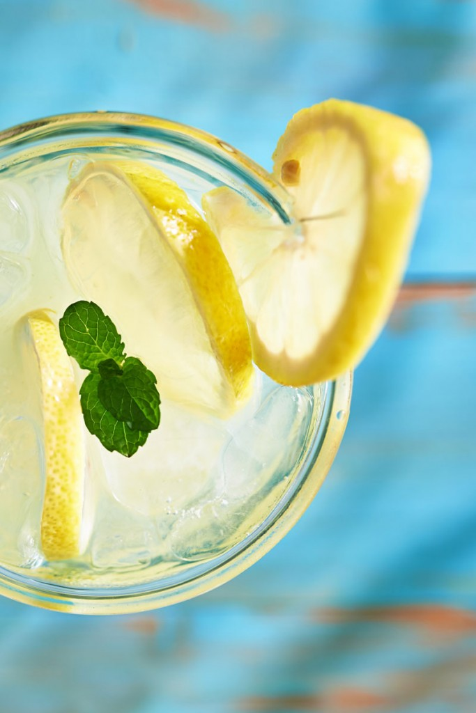 A fresh drink close up with a slice of lemon and mint leaf on top
