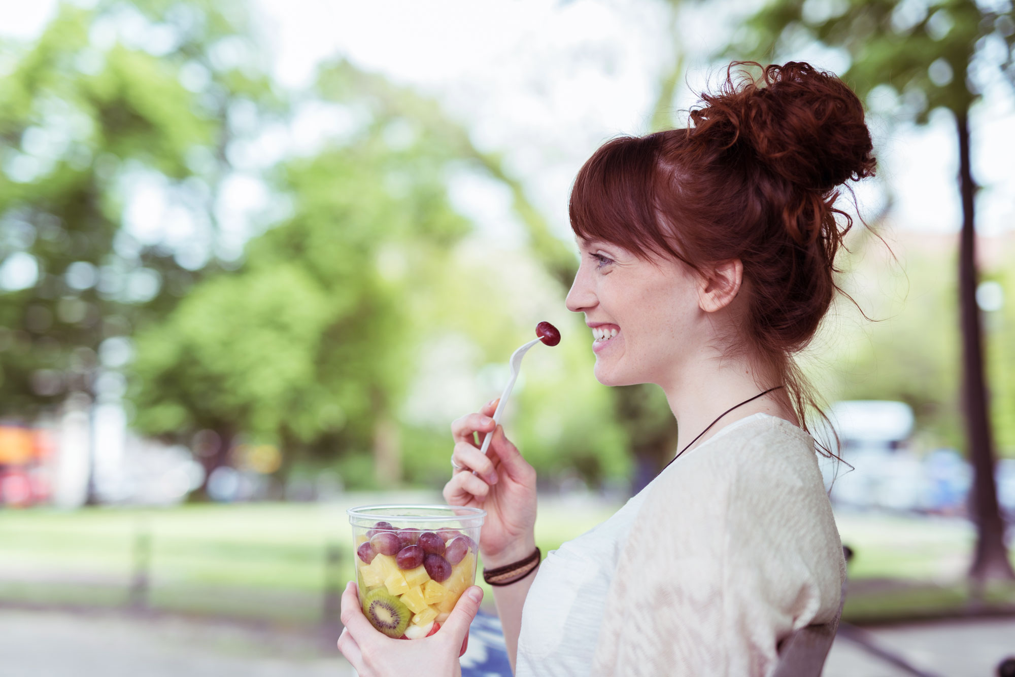 A happy woman enjoying a cup of fruit in park background