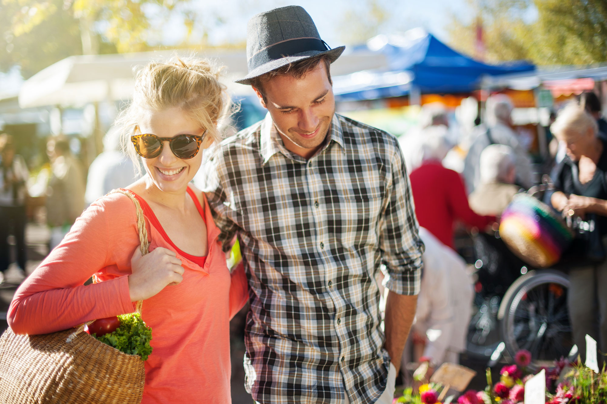 happy couple with casual clothes holding together side by side and enjoying outside at the market