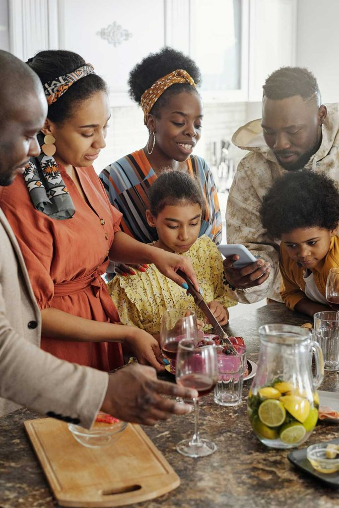 a family standing around the kitchen counter making a pitcher water with fresh citrus fruit
